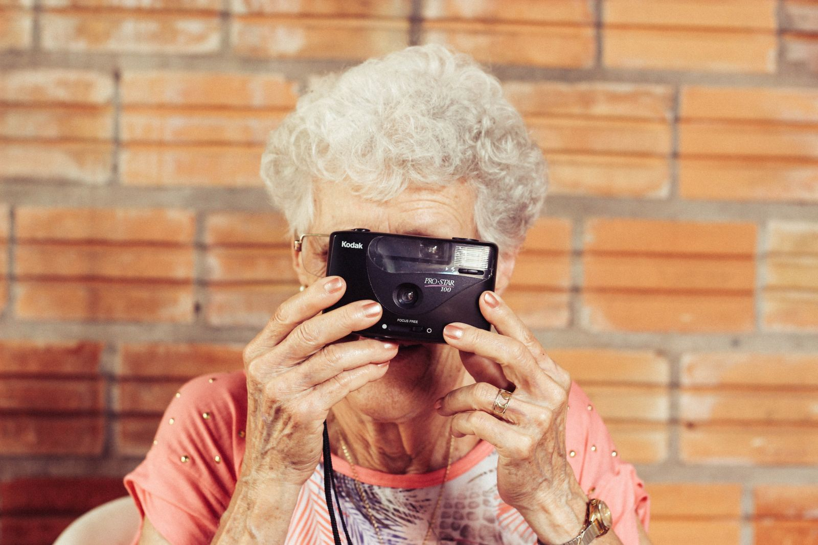 An older woman holds up a camera in front of her face