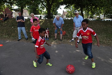 Older people watch children playing football