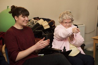 A younger and an older person enjoying an activity by Wyldwood Arts